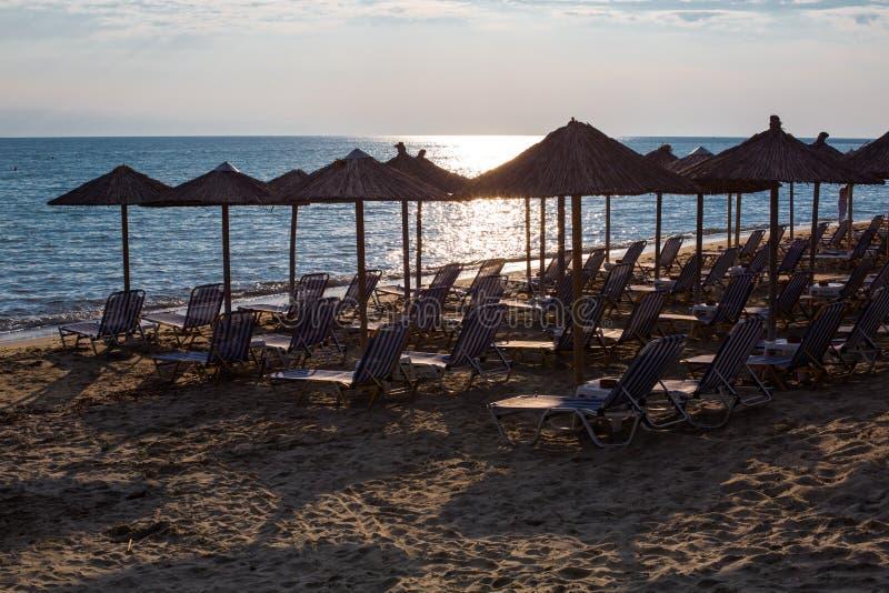 Υπόλοιπος κόσμος των ξύλινων ομπρελών στην αμμώδη παραλία, θάλασσα κατά τη διάρκεια του ηλιοβασιλέματος στοκ φωτογραφία με δικαίωμα ελεύθερης χρήσης