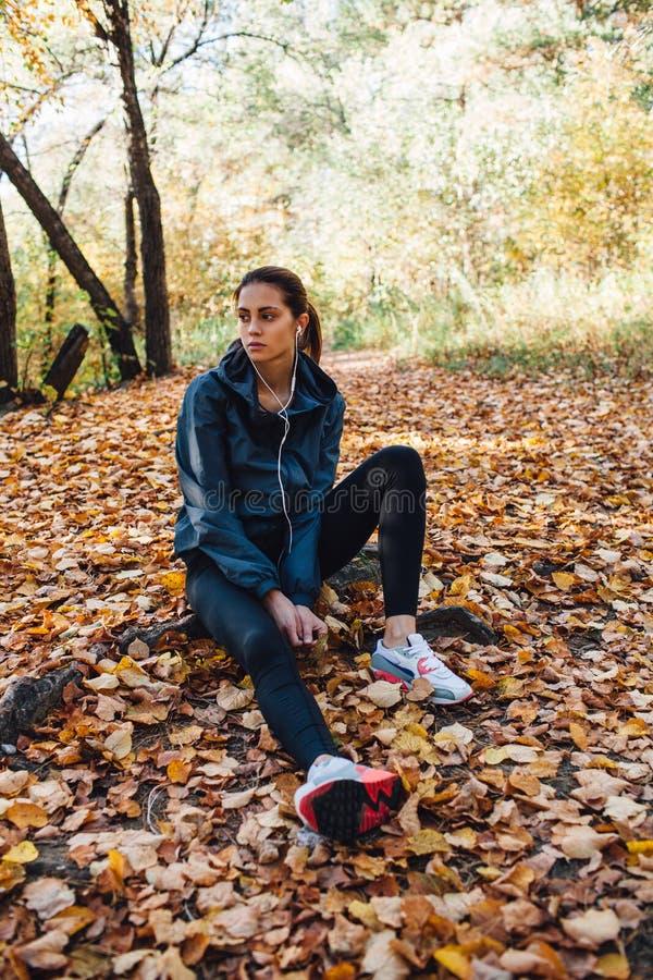 Υπόλοιπο γυναικών δρομέων στα φύλλα στο πάρκο στοκ φωτογραφία με δικαίωμα ελεύθερης χρήσης