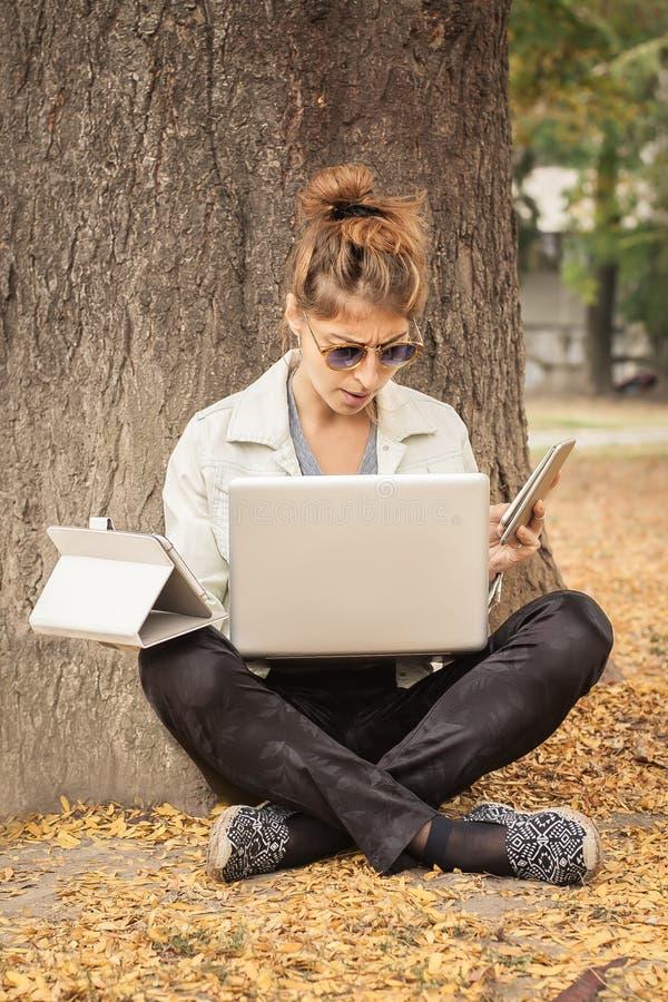 Υστερικό κορίτσι με πάρα πολλές οθόνες, mobils, ταμπλέτες και το lapto στοκ εικόνες