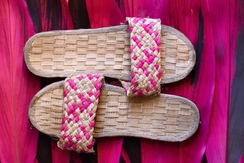 Υφαμένες ροζ παντόφλες στις συστάσεις στοκ φωτογραφία