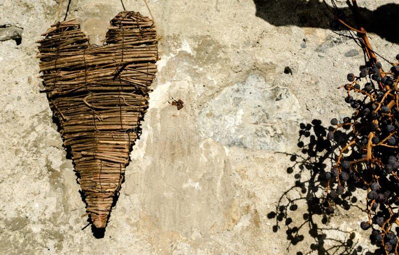 Υφαμένη ξύλινη ένωση καρδιών σε έναν τοίχο βράχου στοκ εικόνα