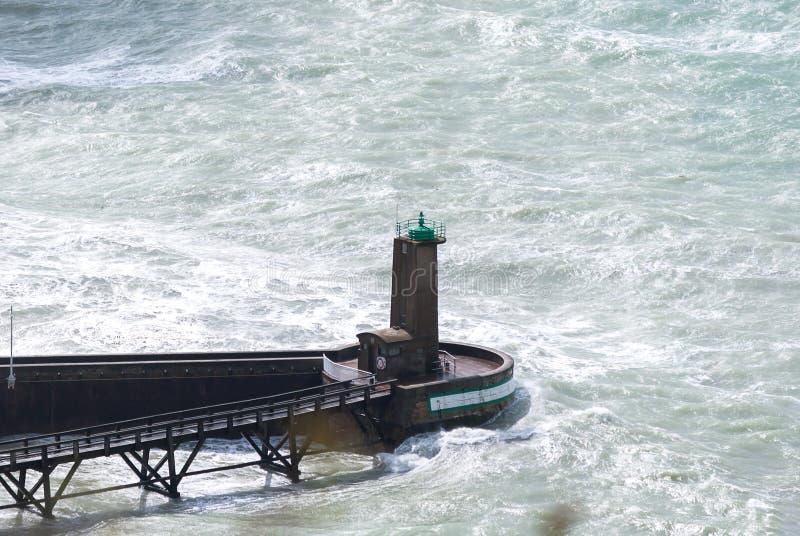 Υψηλά κύματα άποψης που συντρίβουν έναν φάρο κοντά στην ακτή με την μπλε θάλασσα aqua υποβάθρου και τη σκοτεινή ξύλινη γέφυρα, θυ στοκ εικόνα