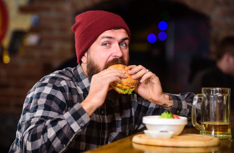 Υψηλά τρόφιμα θερμίδας Εξαπατήστε το γεύμα Εύγευστη burger έννοια Απολαύστε το γούστο φρέσκο burger Το πεινασμένο άτομο Hipster τ στοκ εικόνες με δικαίωμα ελεύθερης χρήσης