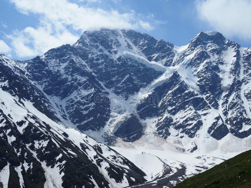 Υψηλά χιονώδη καυκάσια βουνά με έναν παγετώνα με τη μορφή ενός αριθμού επτά αριθμού Αιχμές των βουνών Donguz στοκ φωτογραφίες με δικαίωμα ελεύθερης χρήσης