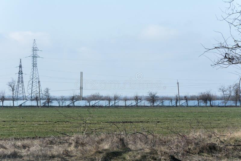 Υψηλής τάσεως ηλεκτροφόρα καλώδια πύργων και γραμμές ηλιακών πλαισίων στοκ φωτογραφίες