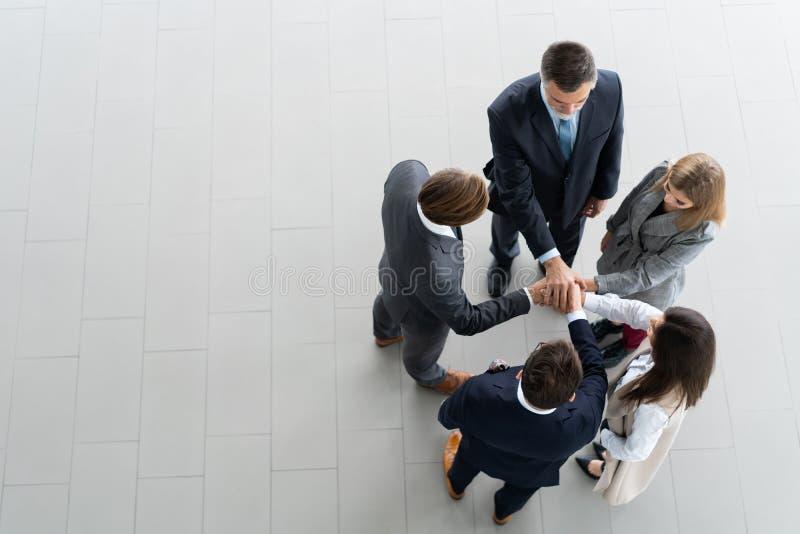 Υψηλή άποψη γωνίας μιας ομάδας των ενωμένων συναδέλφων που στέκονται με τα χέρια τους μαζί σε μια συσσώρευση στο σύγχρονο γραφείο στοκ φωτογραφία με δικαίωμα ελεύθερης χρήσης