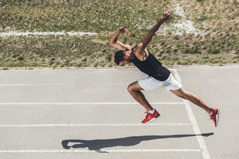 υψηλή άποψη γωνίας του αρσενικού sprinter που απογειώνεται από τη χαμηλή έναρξη στοκ φωτογραφία