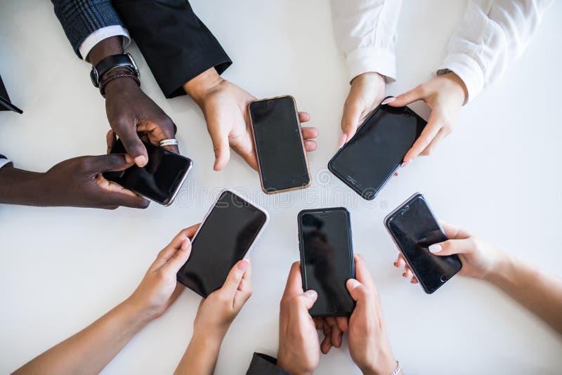 Υψηλή άποψη γωνίας του χεριού Businesspeople που χρησιμοποιεί τα κινητά τηλέφωνα Εθισμός στα δίκτυα στοκ εικόνες