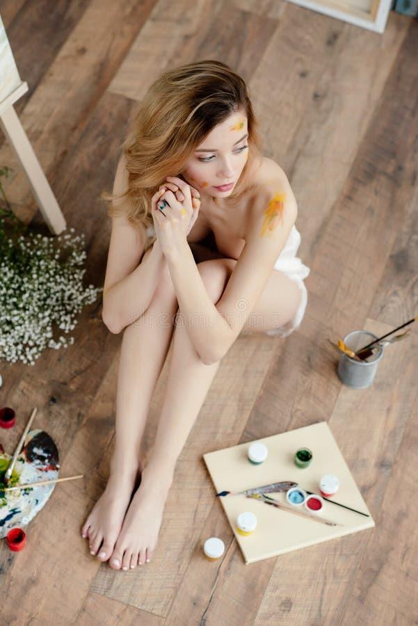 υψηλή άποψη γωνίας του όμορφου αισθησιακού γυμνού καλλιτέχνη με το χρώμα στο πρόσωπο και τη συνεδρίαση σωμάτων στο πάτωμα στοκ εικόνες