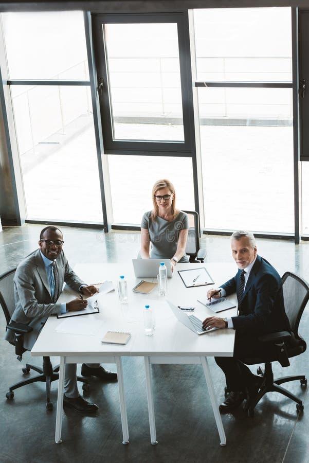 υψηλή άποψη γωνίας των επαγγελματικών multiethnic επιχειρηματιών που χαμογελούν στη κάμερα καθμένος από κοινού στοκ φωτογραφία