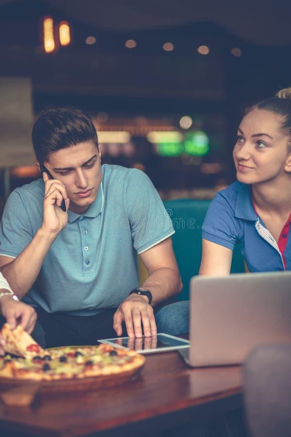 Υψηλή άποψη γωνίας των νέων που τρώνε την πίτσα εργαζόμενων από κοινού στοκ εικόνα με δικαίωμα ελεύθερης χρήσης