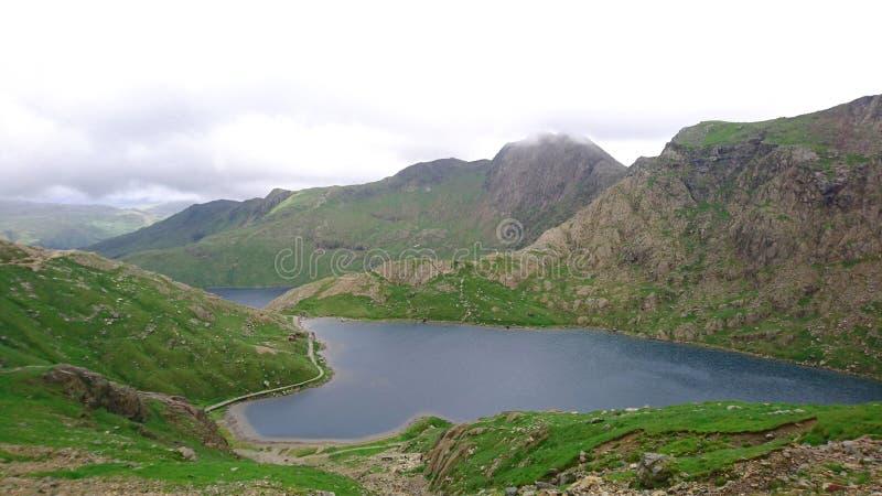 Υψηλή άποψη που κοιτάζει κάτω από πέρα από τη λίμνη στο ίχνος PYG στο υποστήριγμα Snowdon στο εθνικό πάρκο Snowdonia, Ουαλία, UK στοκ φωτογραφία