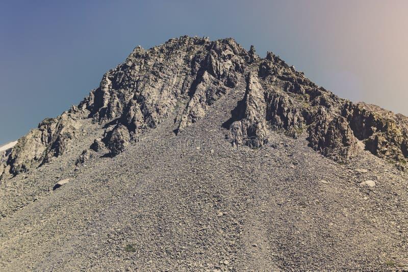 Υψηλή κορυφή του βουνού με την πέτρα χαλαρή Επικίνδυνη rockfall ή καθίζηση εδάφους Πέτρινο μεταλλοφόρο κοίτασμα στοκ εικόνες