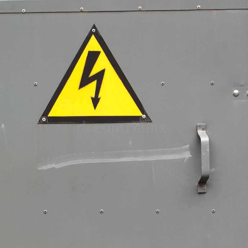 Υψηλή τάση προσοχής σημαδιών στην πόρτα μετάλλων στοκ φωτογραφία