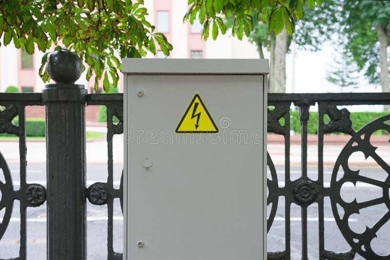 Υψηλή τάση τηλεφωνικών κέντρων σε μια οδό Σημάδι της αστραπής στην ασπίδα στοκ εικόνες με δικαίωμα ελεύθερης χρήσης