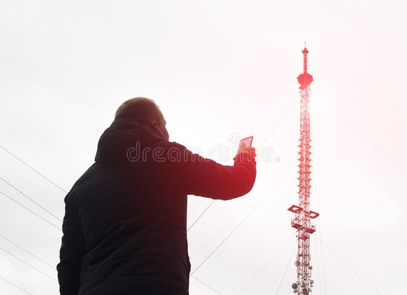Υψηλός κινητός πύργος τηλεπικοινωνιών από τον οποίο υπάρχει ακτινοβολία και ένα άτομο με ένα κινητό τηλέφωνο, φτωχό δίκτυο, διαμό στοκ εικόνα