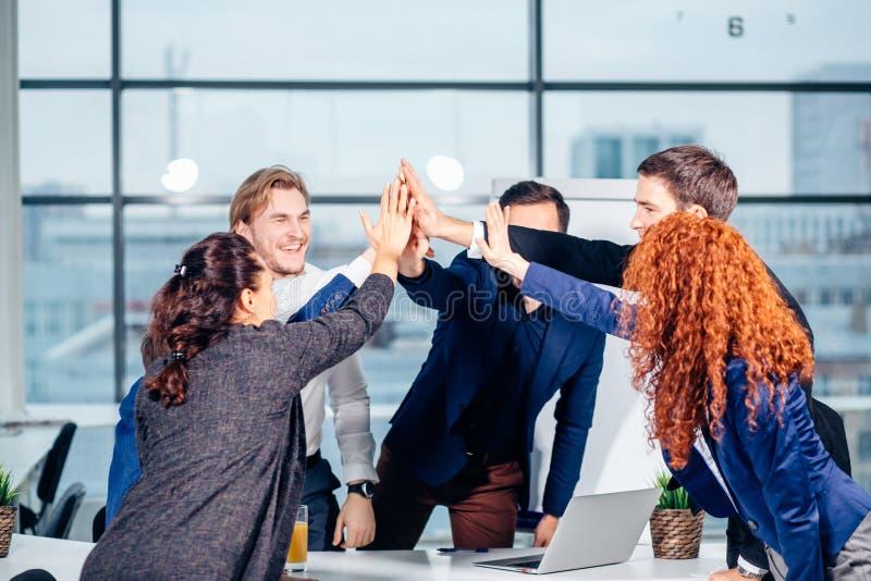 Υψηλός-πέντε νέοι επιχειρηματίες που δίνουν υψηλός-πέντε στη συνάντηση στην αρχή στοκ εικόνες