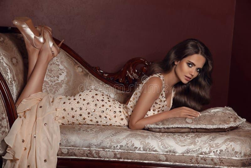 Υψηλό εσωτερικό πρότυπο γυναικών brunette μόδας στα κομψά μπεζ dres στοκ εικόνα