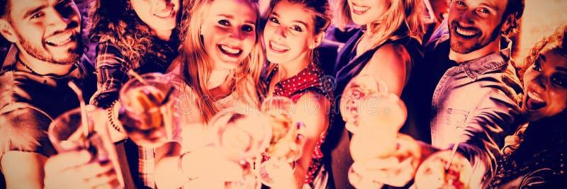 Υψηλό πορτρέτο γωνίας των φίλων με τα ποτά στοκ εικόνα