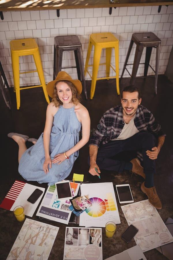 Υψηλό πορτρέτο γωνίας των χαμογελώντας νέων δημιουργικών επαγγελματιών που κάθονται στο πάτωμα με τα φύλλα στοκ εικόνες με δικαίωμα ελεύθερης χρήσης