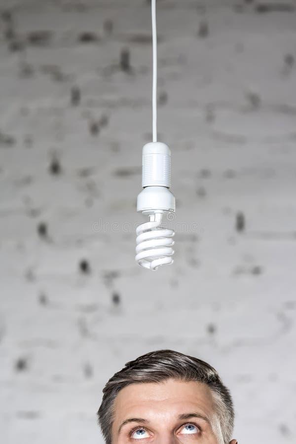Υψηλό τμήμα του στοχαστικού ώριμου επιχειρηματία που εξετάζει ένωση ενεργειακού την αποδοτική lightbulb ενάντια στο τουβλότοιχο σ στοκ φωτογραφία με δικαίωμα ελεύθερης χρήσης