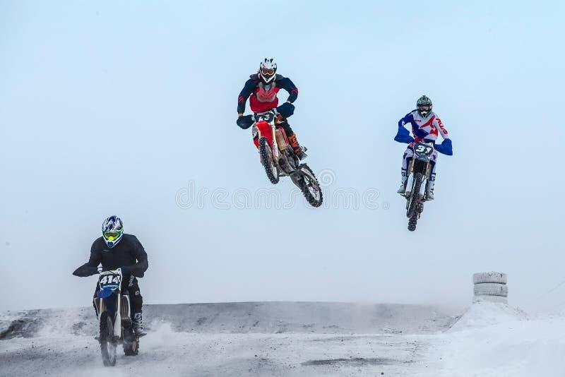 Υψηλά άλματα και αναβάτες πτήσης στη μοτοσικλέτα στο χειμερινό μοτοκρός στοκ εικόνα με δικαίωμα ελεύθερης χρήσης