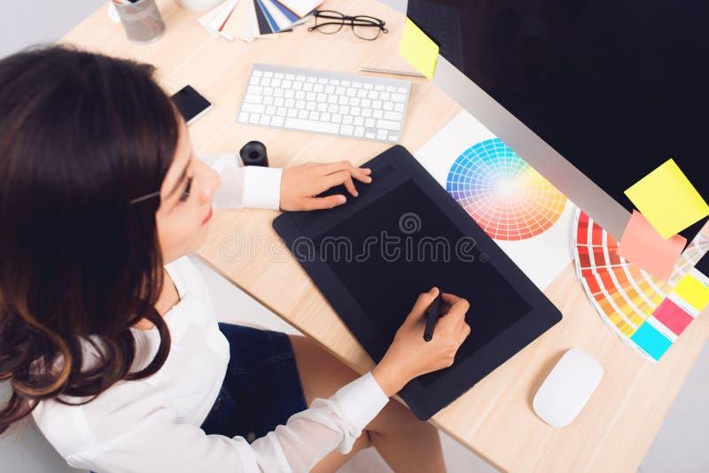 Υψηλή άποψη γωνίας ενός συντάκτη φωτογραφιών που εργάζεται στο γραφείο σε δημιουργικό στοκ εικόνα με δικαίωμα ελεύθερης χρήσης