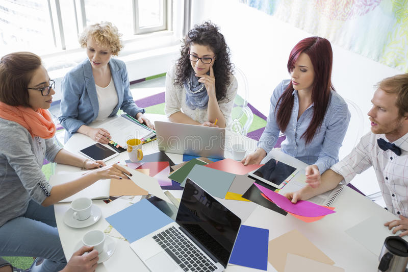 Υψηλή άποψη γωνίας του businesspeople που αναλύει τις φωτογραφίες στο δημιουργικό γραφείο στοκ φωτογραφία