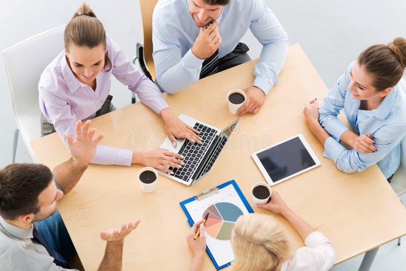 Υψηλή γωνία των επιχειρηματιών στον πίνακα στοκ φωτογραφία