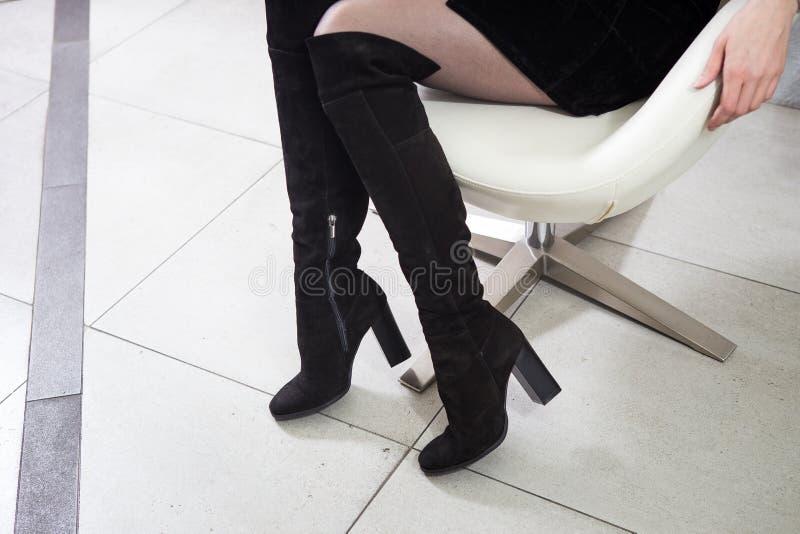 Υψηλό μαύρο γόνατο μποτών σουέτ κοριτσιών υψηλό σε μια άσπρη καρέκλα στοκ εικόνες