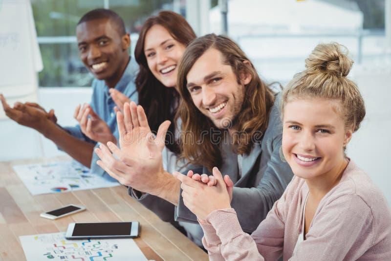 Υψηλό πορτρέτο γωνίας των χαμογελώντας επιχειρηματιών που χτυπούν στο γραφείο στοκ φωτογραφίες