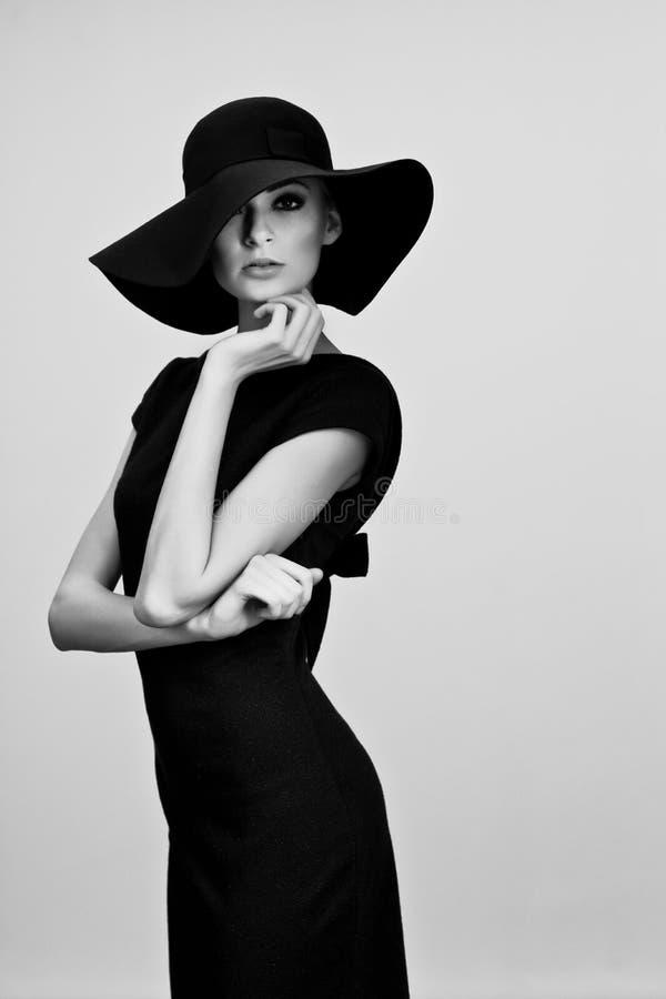 Υψηλό πορτρέτο μόδας της κομψής γυναίκας στο γραπτό καπέλο στοκ εικόνα με δικαίωμα ελεύθερης χρήσης