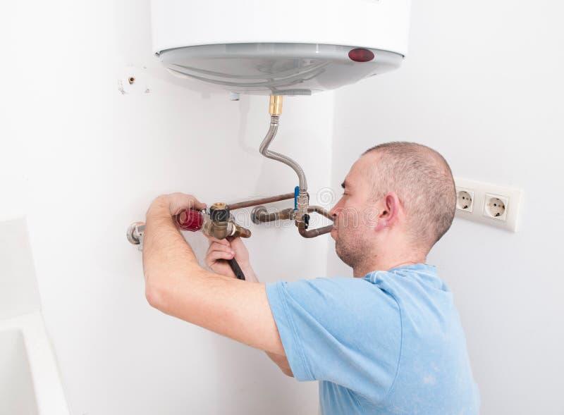 Υδραυλικός που επισκευάζει έναν ηλεκτρικό λέβητα στοκ φωτογραφίες
