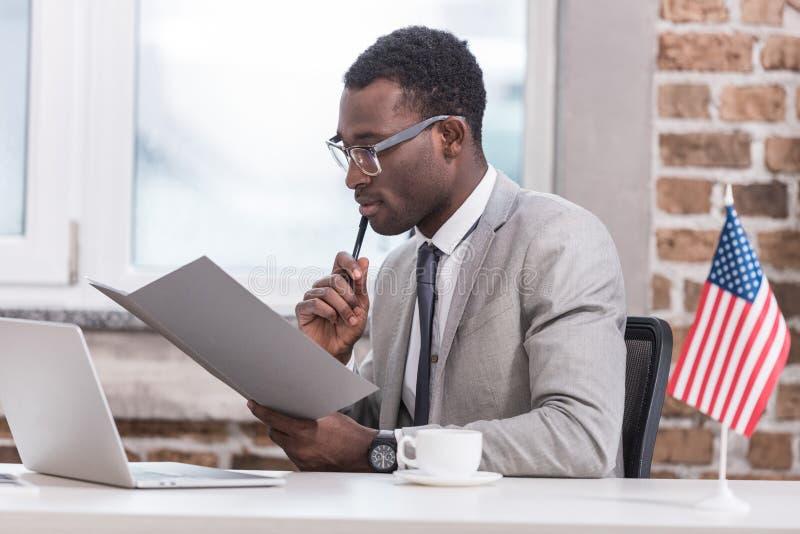 Φάκελλος και συνεδρίαση εκμετάλλευσης επιχειρηματιών αφροαμερικάνων στοκ εικόνα με δικαίωμα ελεύθερης χρήσης