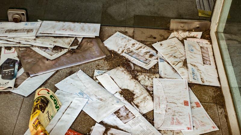 Φάκελοι και περιοδικά μπροστά από την πόρτα, που καλύπτεται με τη σκόνη στοκ φωτογραφίες