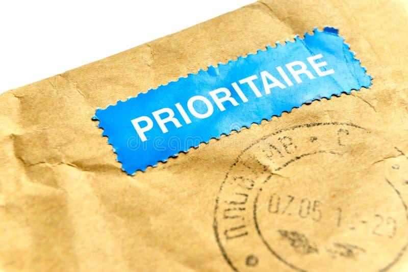 Φάκελος με την μπλε αυτοκόλλητη ετικέττα ταχυδρομείου prioritaire στοκ εικόνες