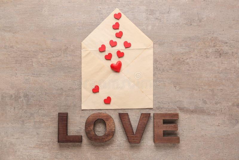 Φάκελος με τις καρδιές και ΑΓΑΠΗ λέξης που συντίθεται από τις επιστολές στον πίνακα στοκ φωτογραφίες με δικαίωμα ελεύθερης χρήσης