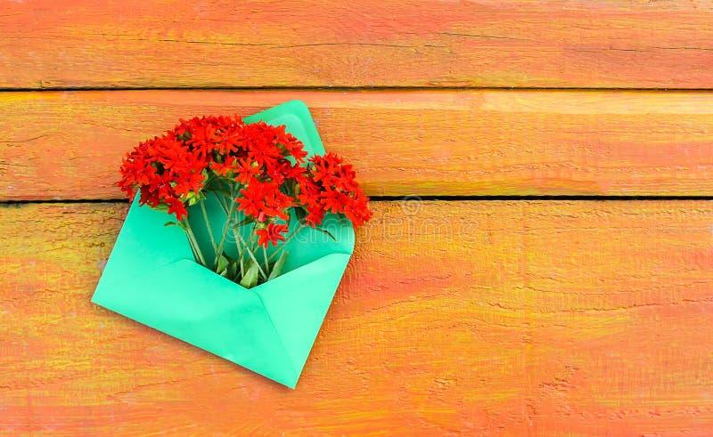 Φάκελος Πράσινης Βίβλου με τα φρέσκα λουλούδια lychnis κήπων κόκκινα στο ξύλινο υπόβαθρο Εορταστικό floral πρότυπο Σχέδιο ευχετήρ στοκ φωτογραφία με δικαίωμα ελεύθερης χρήσης