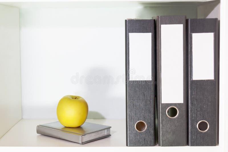 Φάκελλοι για τα έγγραφα, τον αρμόδιο για το σχεδιασμό και το πράσινο μήλο σε ένα ράφι βιβλίων στοκ φωτογραφία με δικαίωμα ελεύθερης χρήσης