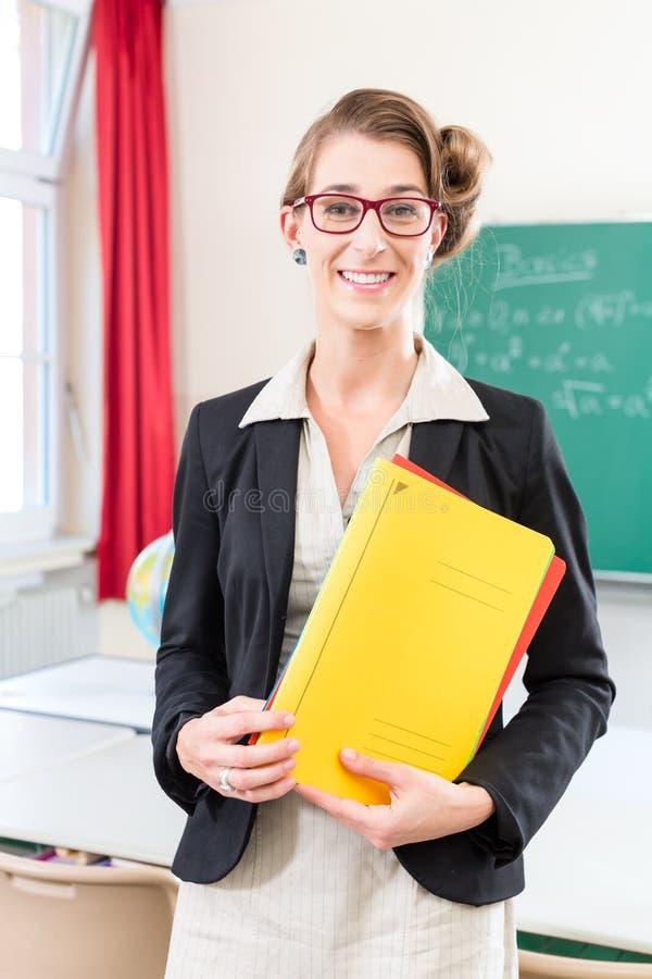 Φάκελλος εκμετάλλευσης δασκάλων στο σχολείο μπροστά από μια κατηγορία στοκ εικόνες με δικαίωμα ελεύθερης χρήσης