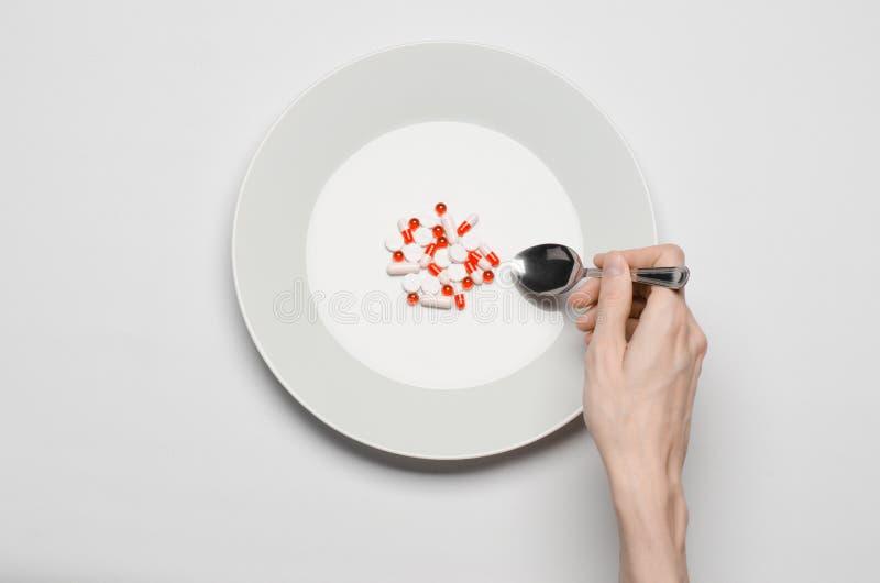Φάρμακα και ανάρμοστο θέμα διατροφής: το ανθρώπινο χέρι κρατά ένα πιάτο με τα χάπια που απομονώνονται στην άσπρη τοπ άποψη υποβάθ στοκ φωτογραφίες