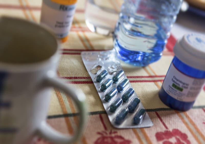 Φάρμακο κατά τη διάρκεια του προγεύματος, κάψες δίπλα σε ένα ποτήρι του νερού στοκ εικόνες με δικαίωμα ελεύθερης χρήσης
