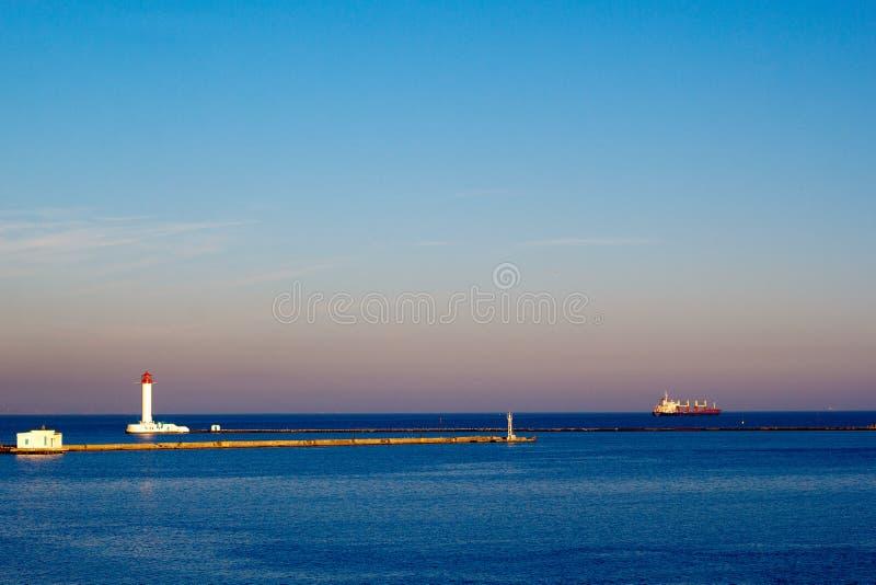 Φάρος και φορτηγό πλοίο που αφήνουν ένα λιμάνι στοκ φωτογραφία