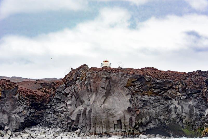 Φάρος πέρα από τους βράχους βασαλτών, νησί Heimaey, Ισλανδία στοκ εικόνα
