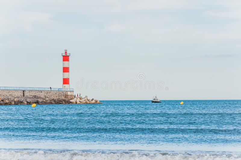 Φάρος του Port-la-Nouvelle κόκκινος και άσπρος στο νεφελώδη ουρανό στοκ εικόνες