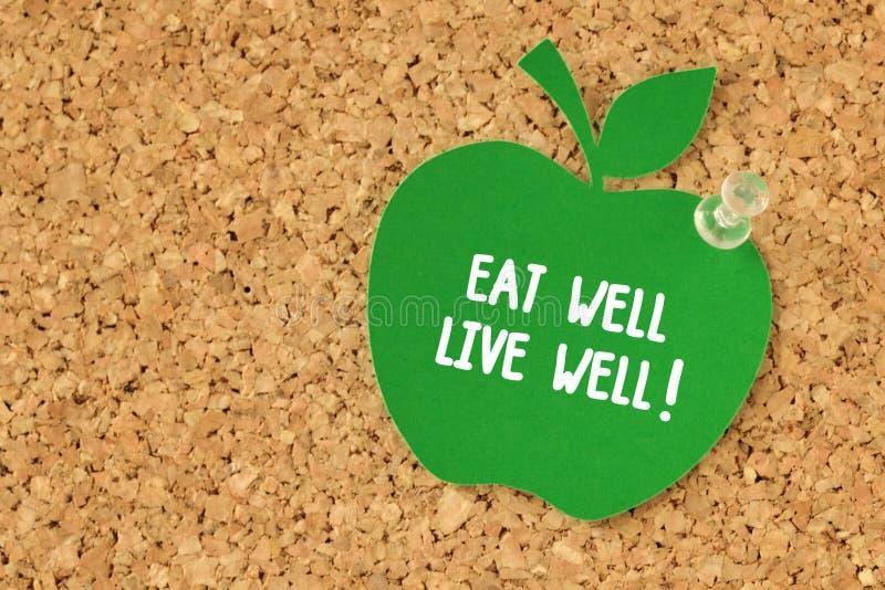 Φάτε καλά, ζήστε καλά! γραπτός στη με σχήμα μήλου σημείωση εγγράφου για το pinbo στοκ φωτογραφία με δικαίωμα ελεύθερης χρήσης