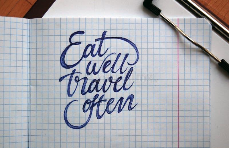 Φάτε καλά και ταξιδεψτε το συχνά καλλιγραφικό υπόβαθρο στοκ φωτογραφίες