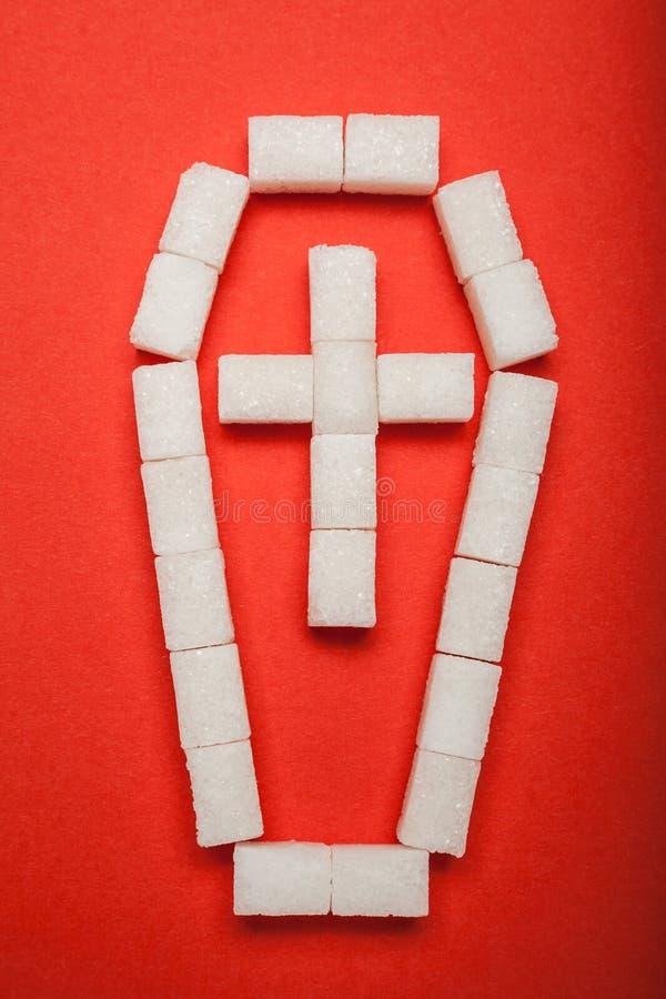 Φέρετρο με έναν σταυρό των κύβων της ζάχαρης σε ένα κόκκινο υπόβαθρο Ανθυγειινή κατανάλωση στοκ εικόνες