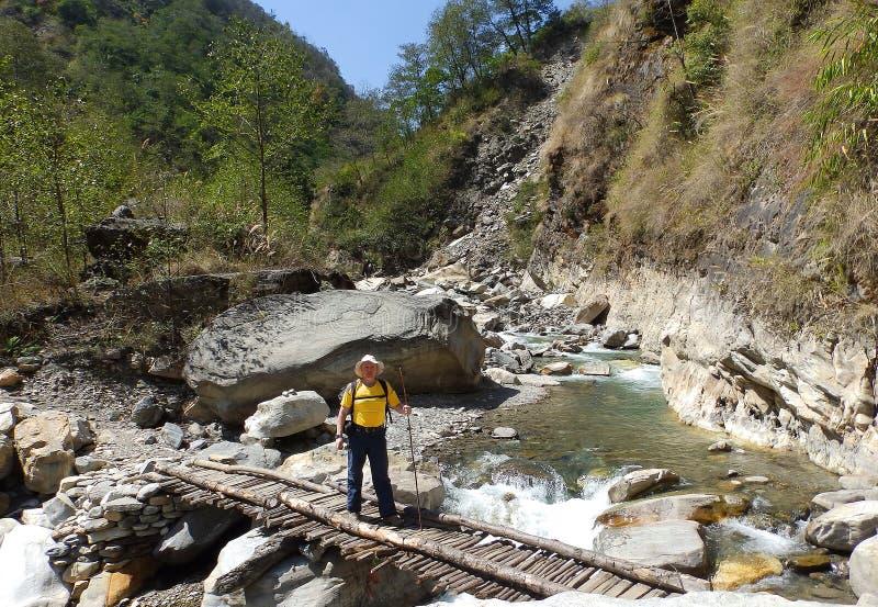 Φέρνοντας αγαθά πέρα από την ξύλινη γέφυρα στο στρατόπεδο βάσεων Everest στοκ φωτογραφία