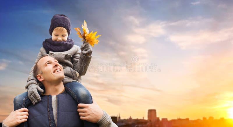 Φέρνοντας γιος πατέρων με τα φύλλα φθινοπώρου στην πόλη στοκ εικόνες με δικαίωμα ελεύθερης χρήσης